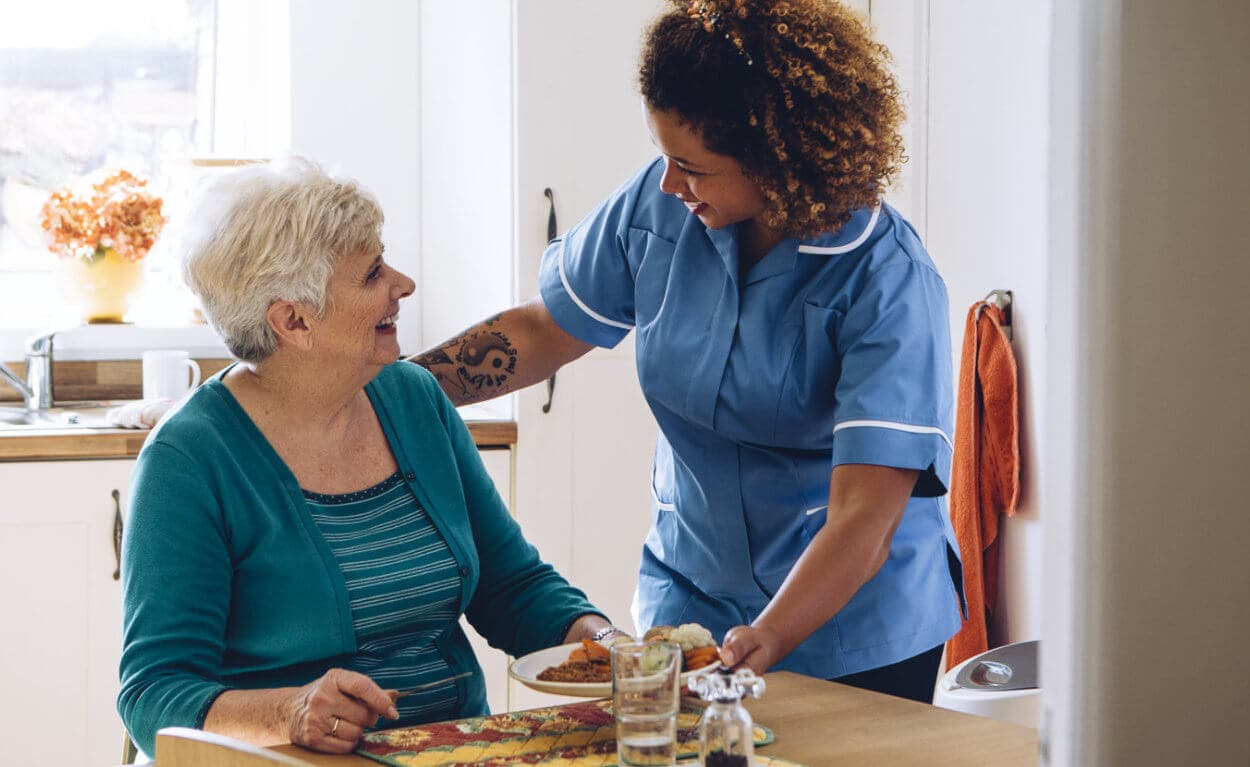 caregiver serving meal to old woman