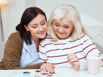 caregiver helping elderly woman to complete jigsaw puzzle