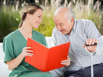 Smiling female nurse looking at senior man while reading book