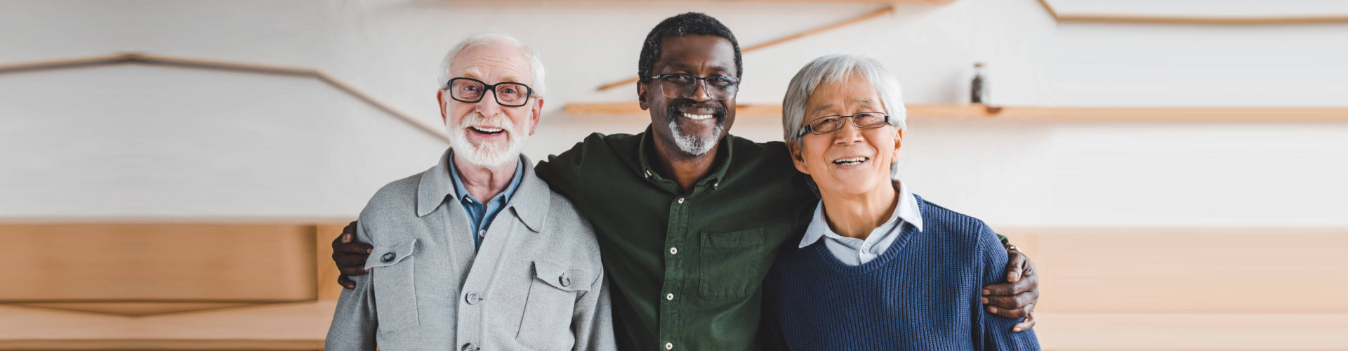 Three men smiling standing side by side