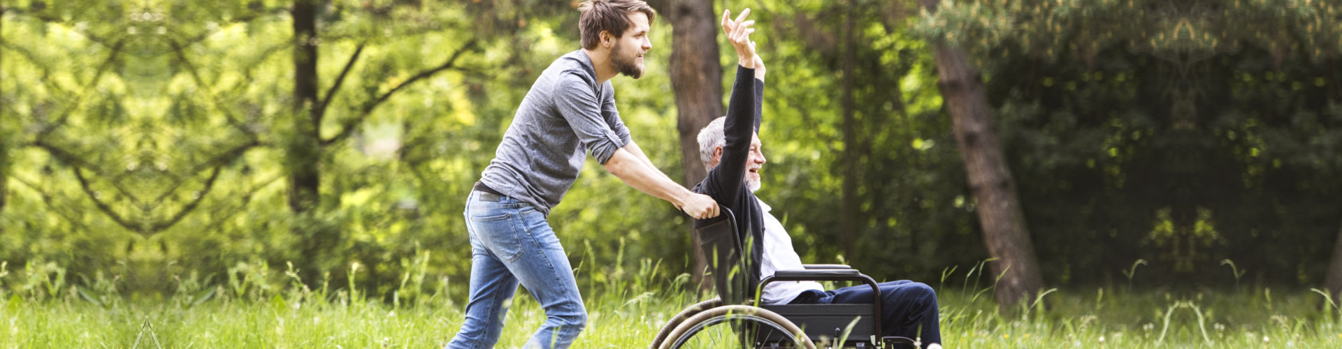 Elderly man raising both arms being so happy while being pushed in wheelchair by a caregiver