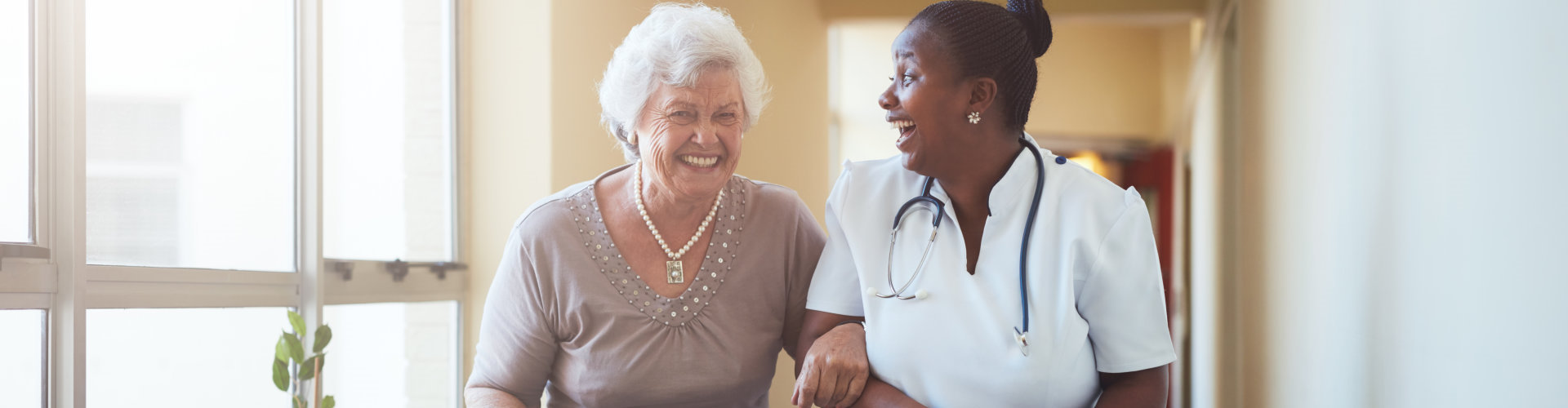 caregiver and old woman walking on a hallway